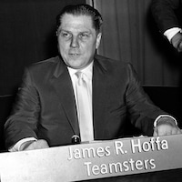 Photo en noir et blanc d'un homme assis devant une affiche avec l'inscription James R. Hoffa Teamsters.