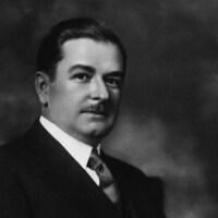 Maurice Duplessis est vêtu d'un veston et d'une cravate.
