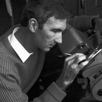 Gros plan sur Norman McLaren en train de manipuler de la machinerie de création.