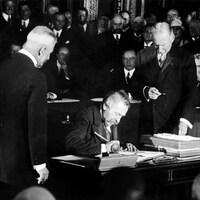 Photo en noir et blanc d'un homme moustachu qui signe un document assis. Deux hommes debout l'entourent dans une salle avec d'autres hommes.
