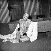 Un homme maquillé de manière horrible est assis devant un cercueil.