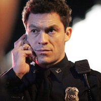 Un policier en uniforme parle au cellulaire.