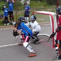 Des enfants jouent au hockey dans la rue.