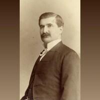 Portrait en noir et blanc d'un homme portant une moustache.