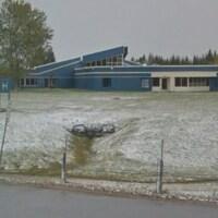 Un long édifice bleu dans un champ sur le bord de la route.