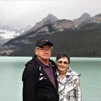 Portait du couple devant de grandes montagnes et un lac.