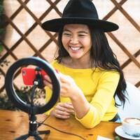 Une jeune femme sourit en regardant son téléphone. Elle est assise à une table sur laquelle se trouvent une lampe en forme de cercle et un café.