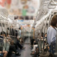 Des hommes et des femmes, photographiés de manière floue, dans une rame de métro.