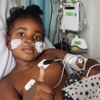 Une petite fille dans son lit d'hôpital fait signe de bien aller avec un pouce levé vers le haut.