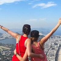 Deux femmes font dos à la caméra en regardant le paysage du sommet de la colline.