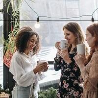 Trois femmes prennent un café. Les logos de Quartier d'affaires, de la Fédération des gens d'affaires francophones et du Gouvernement de la province de l'Ontario sont au haut de l'image.