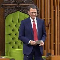 Un homme debout devant une chaise verte.