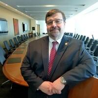 Robert Haché devant une grande table dans une salle de réunion.