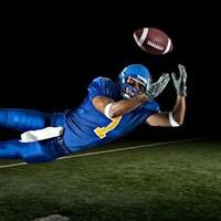 Un joueur s'élance pour attraper un ballon de football.