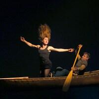Dans un canot, une femme est à genoux et a les cheveux dressés sur la tête, tandis qu'un homme rame.