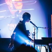 Klô Pelgag joue du piano et chante au micro lors d'un spectacle.