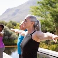 Un groupe de personnes pratiquant le yoga à l'extérieur.