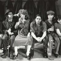 Six hommes et femmes en costumes d'époque sont assis sur un banc.