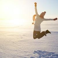 Une femme qui saute dans la neige.