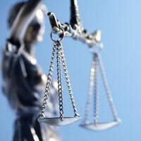 Gros plan sur la balance que porte la statue de la Justice.