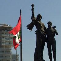 À Beyrouth, le drapeau libanais flotte devant un immeuble en construction.