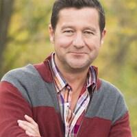 Dany Turcotte pose en regardant la caméra, les bras croisés, sur fond de bois