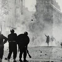 Photo en noir et blanc montrant des policiers face à des citoyens qui leur lance des pavés dans une rue de Paris.