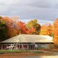 Un bâtiment circulaire devant lequel se trouvent des charpentes de tipis avec un paysage d'automne en arrière-plan.