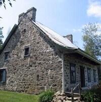 Une maison ancestrale en pierres avec du gazon vert.