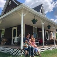 La famille Dallaire pose pour une photo sur la galerie de leur ferme.