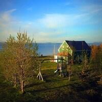 Des arbres entourent une maison verte qui surplombe le Saint-Laurent, aux Îles.