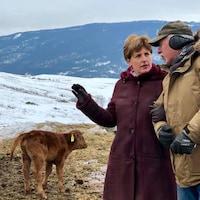La ministre Bibeau qui tient un homme par le bras, avec des bovins et montagnes enneigées en arrière plan.