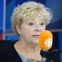 Marie Eykel derrière un micro dans un studio radio de Radio-Canada.