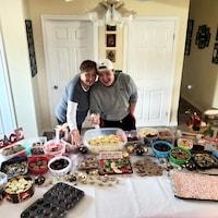 Carey Roy et son petit-fils Connor Lafortune posent fièrement devant une table remplie de biscuits et de pâtisseries.