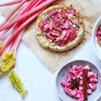 Des tiges de rhubarbe, une tarte salée à la ricotta et à la rhubarbe, des tiges de rhubarbe marinées et une compote de rhubarbe accompagne un bol de smoothie déjeuner.