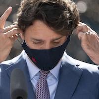 Gros plan de Justin Trudeau qui met son masque après son point de presse.