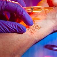 Une main portant un gant, un avant-bras avec un code QR et une seringue avec le vaccin contre la COVID-19.