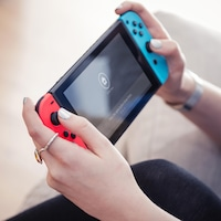 Une personne joue avec une Nintendo Switch.