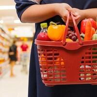 Une dame tient un panier de fruits et légumes dans une épicerie.