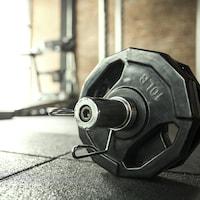 Des poids sur une barre dans une salle d'entraînement.