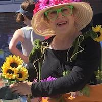 Sylvie Lacombe porte un costume orné de tournesols et un chapeau de paille.