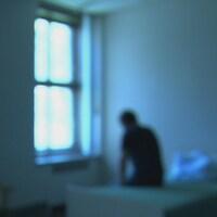 Une image floue d'un homme assis sur un lit dans une petite chambre d'hôpital.