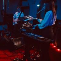 Deux femmes claviéristes et un bassiste en performance dans une cathédrale, sous un éclairage tamisé