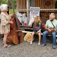 Trois musiciens, une contrebasse et une guitare dehors à la ferme Flying Geese Farm.