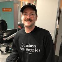 Frank Bach, graphiste principal de l'application mobile Headspace, dans le studio de Sudbury sourit à la caméra vêtue d'un chandail noir et d'une casquette noire