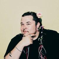 L'artiste pose avec une main sur le menton; il porte une rose dans ses cheveux