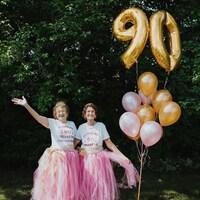 Rolande et Fernande vêtues de tutus roses à côté de ballons gonflables, à l'extérieur.