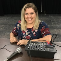 Mélissa Larosse posée derrière une petite console de son dans un local de répétitions