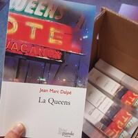 Une main tient une copie de la pièce de théâtre La Queens de Jean Marc Dalpé