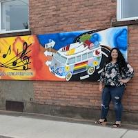 Tracy DeCaen pose devant sa murale; trois panneaux en format paysage accrochés sur un mur de brique